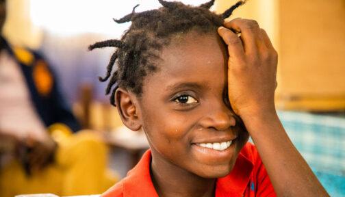 Una bambina sorride mentre si compre l'occhio con la mano.