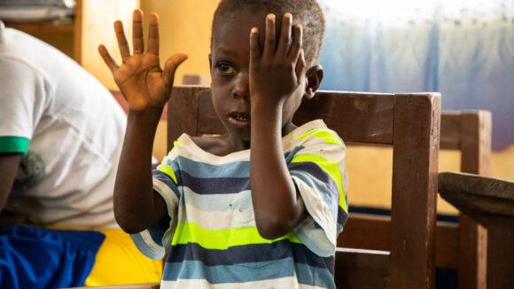 Un bambino si copre un occhio con la mano.
