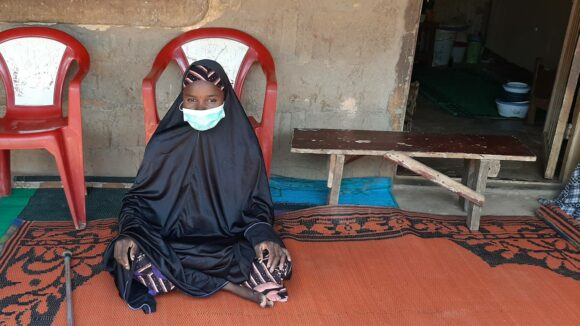 A young woman, wearing a mask, sits on a rug in front of her house by her walking stick